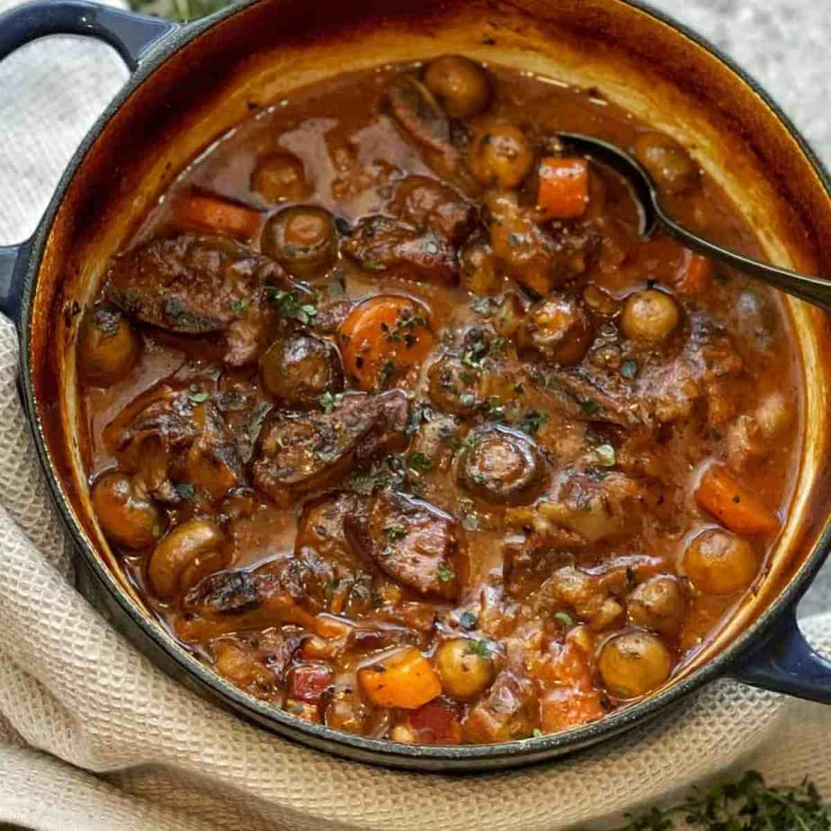 beef stew with mushrooms and carrot in blue pot
