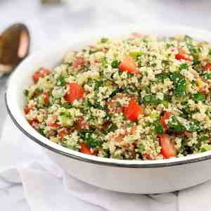 golden grains of couscous and chopped tomato and parsley in a white bowl