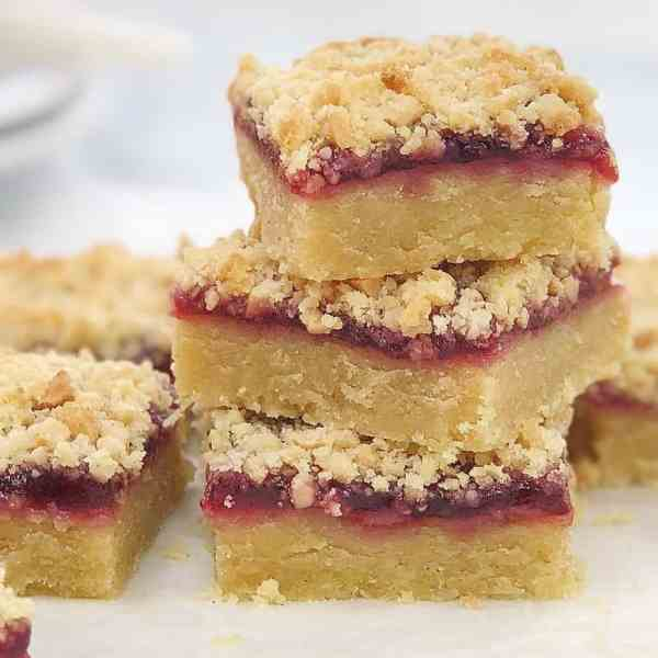 golden shortbread base with a layer of red raspberry jam and golden crumble on top