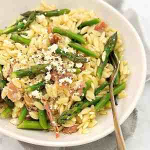 rice shaped pasta with chopped asparagus in a white bowl