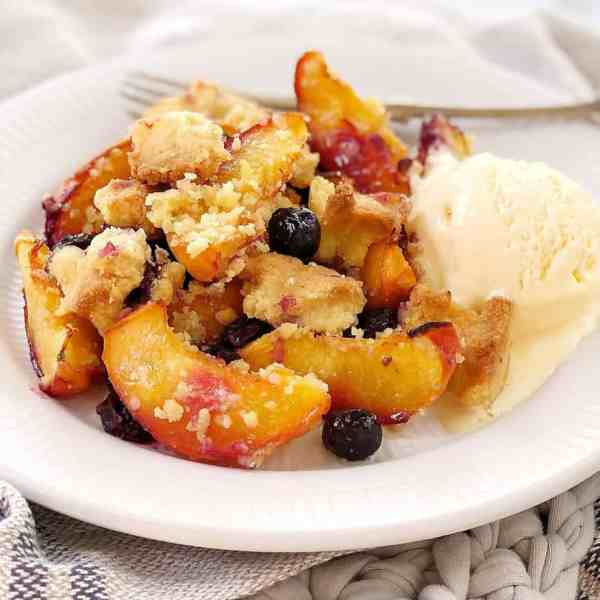 yellow peaches and blueberries with golden crumble topping on a white plate