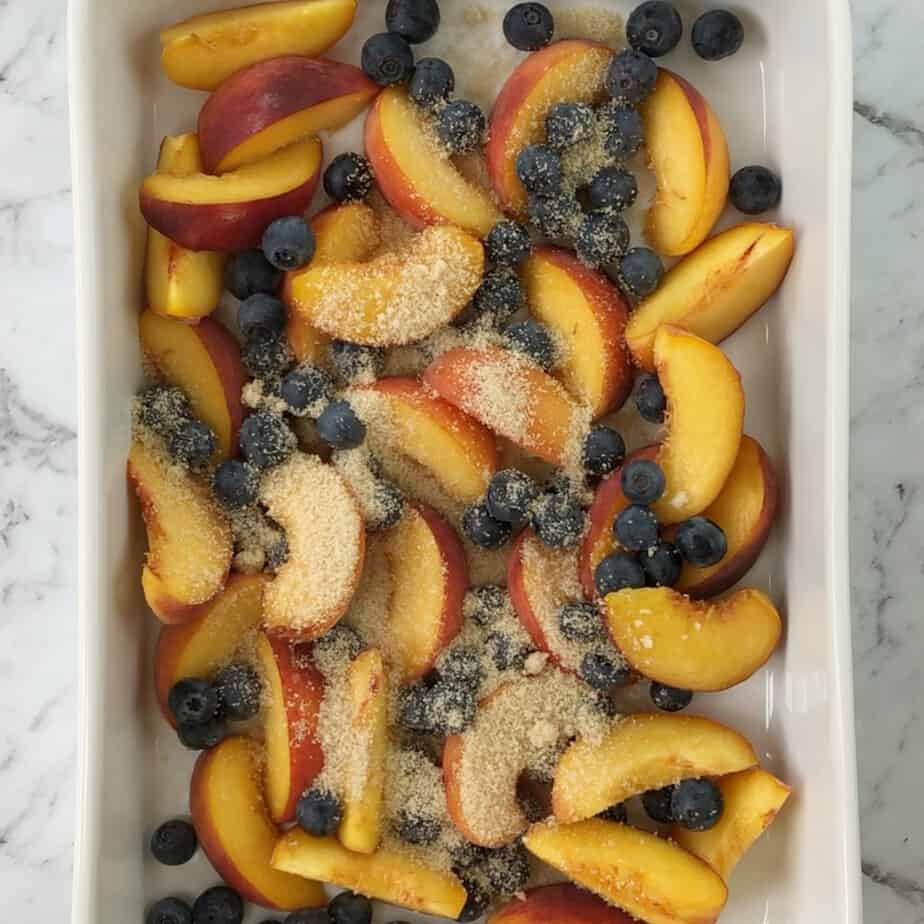 Peach slices and blueberries with sugar on top in a white baking dish