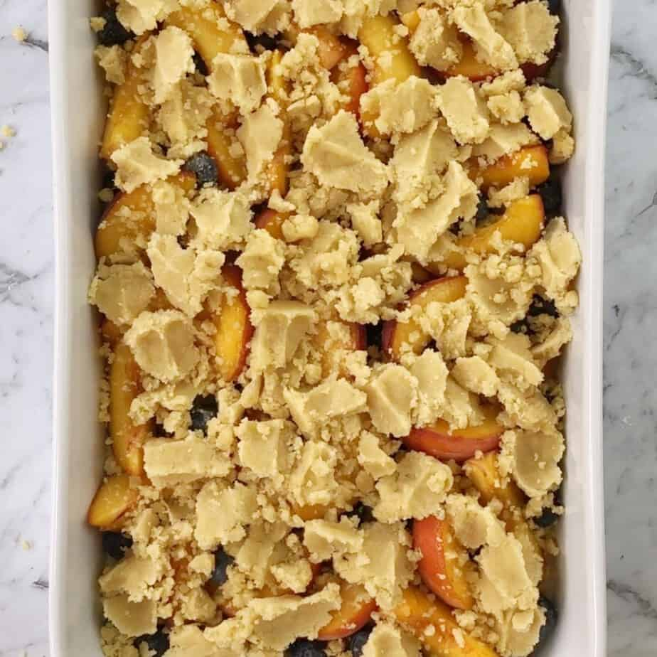 blueberry and peach crumble in white baking dish