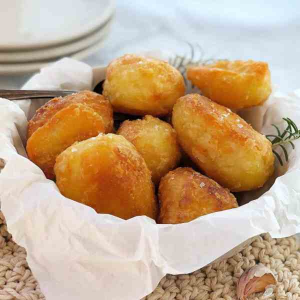 golden roasted potatoes in a white bowl
