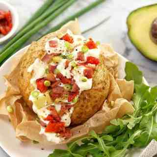 stuffed baked potato on a white plate with green salad