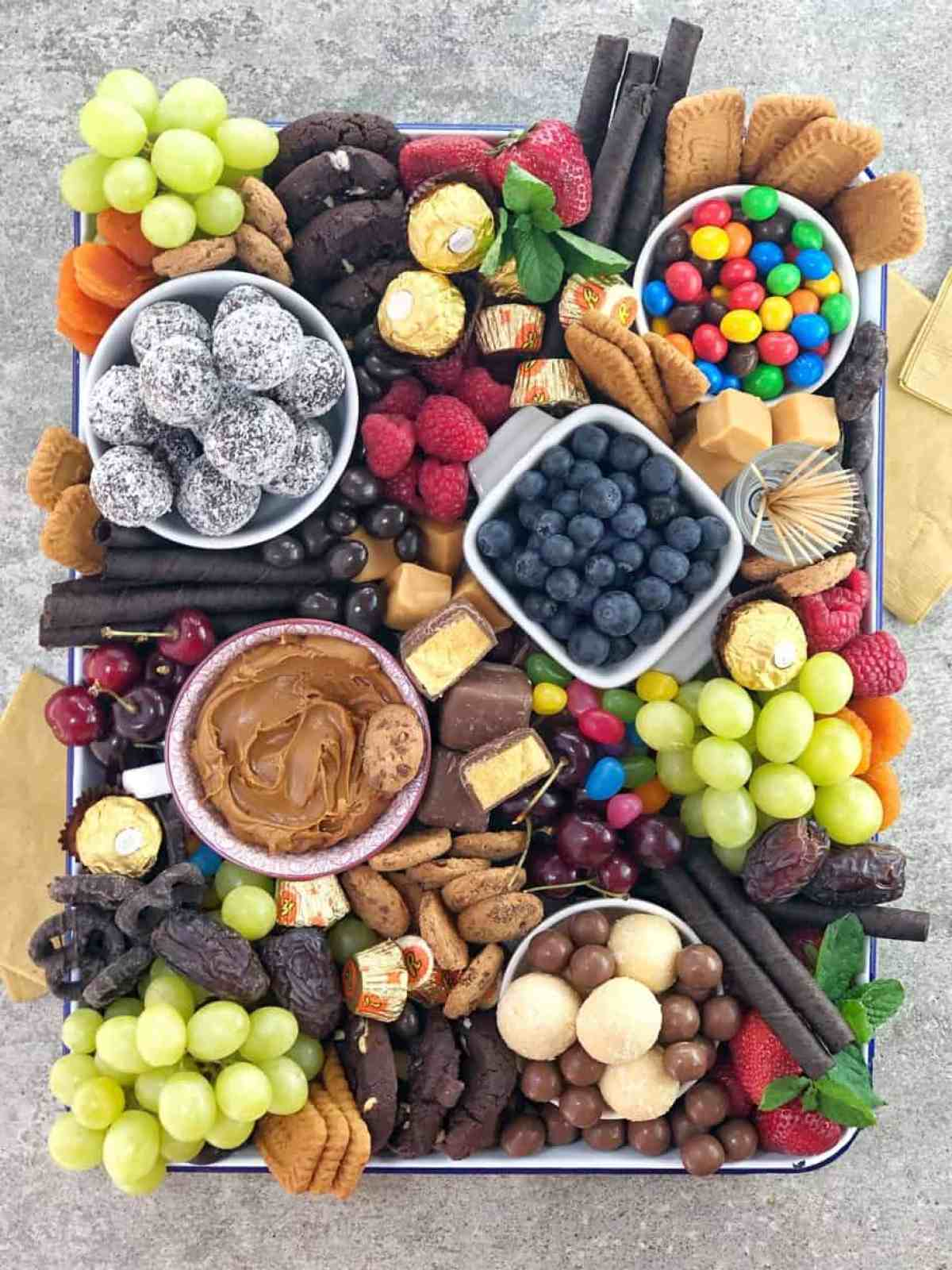 various chocolates sweets and fruit in a white baking dish