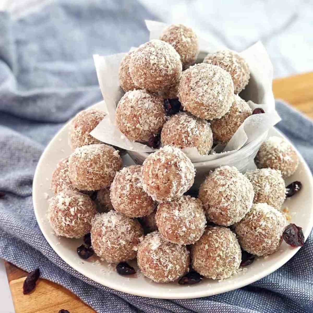 white chocolate and cranberries balls rolled in coconut on a white plate