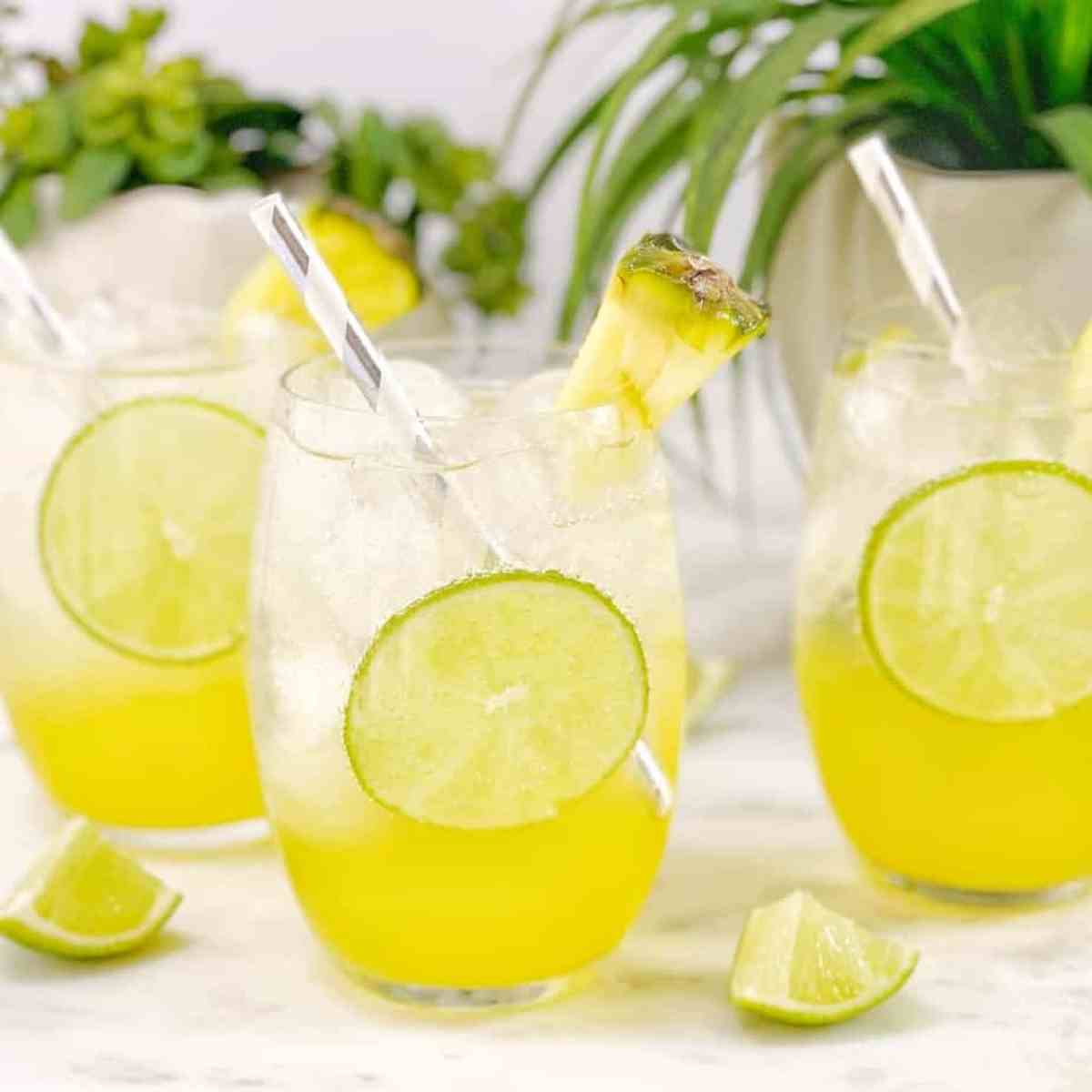 a clear and yellow layered drink with a piece of lime in a clear glass