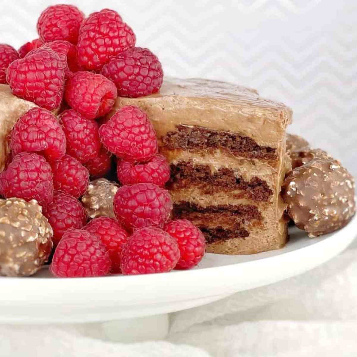 biscuit and cream cake with raspberries on a white plate