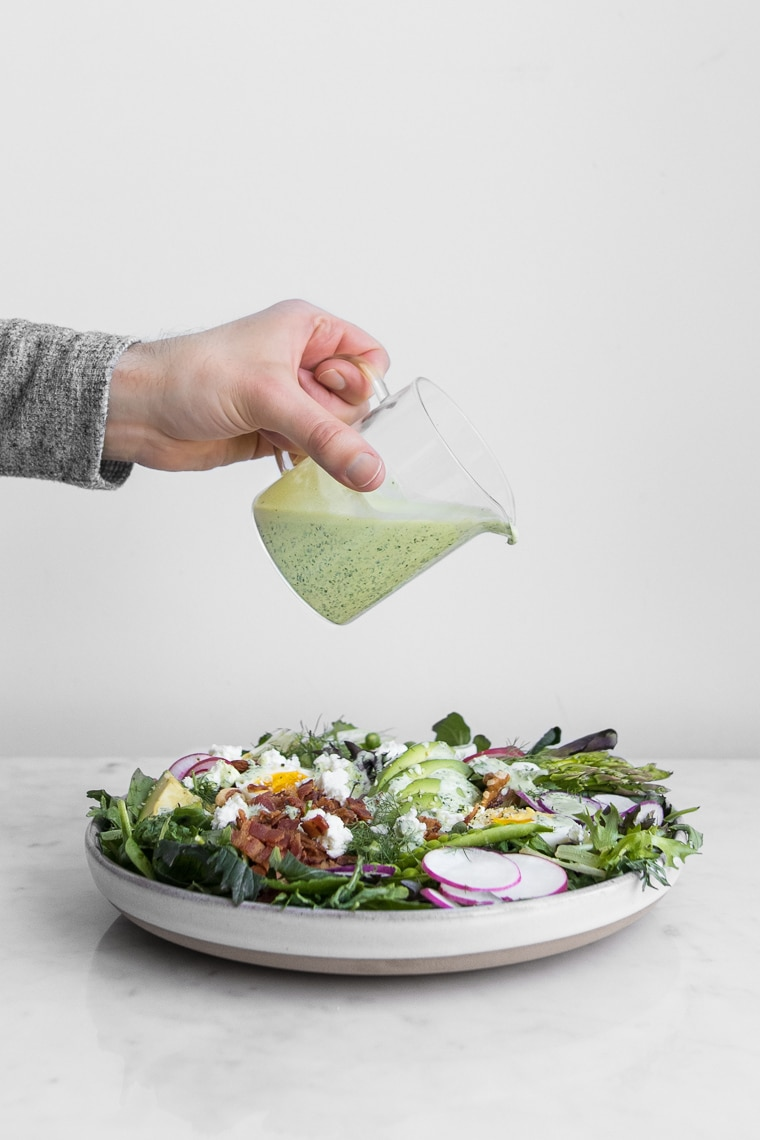 Pouring Green Goddess Dressing on a Salad