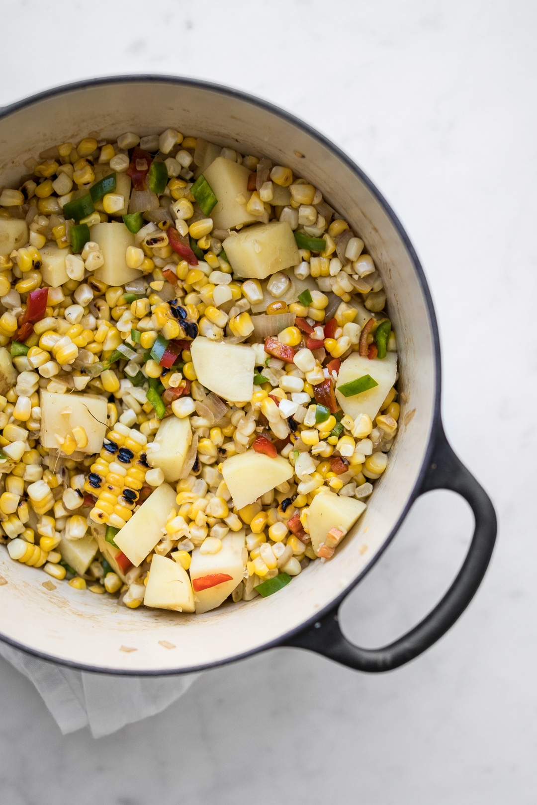 Corn, potatoes, and vegetables cooking in a dutch oven