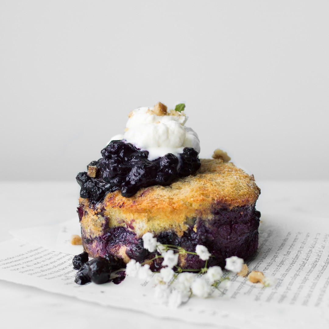 Side view of small Blueberry French Toast Cake topped with whipped cream and next to a sprig of baby's breadth