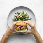 Philip's hands holding a curry fried chicken sandwich above a plate with salad on it
