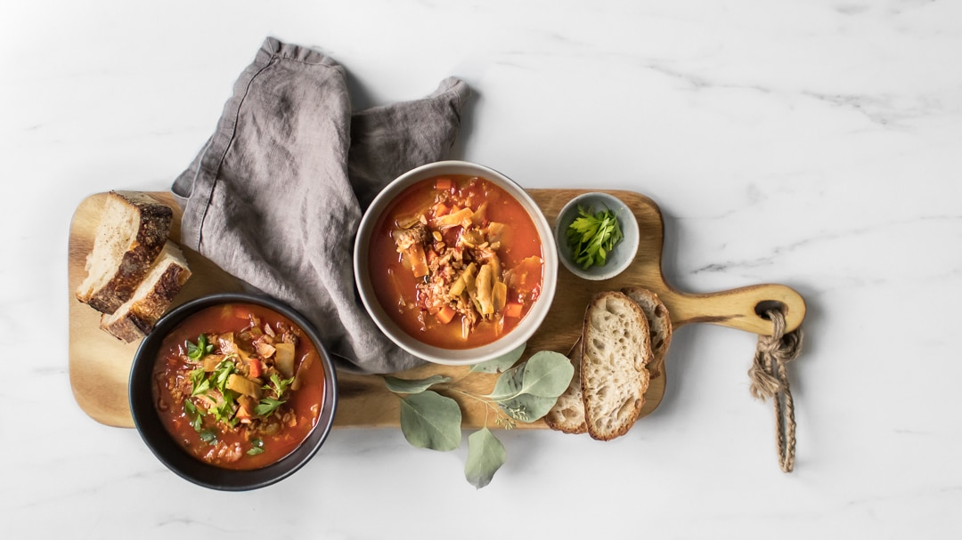 Two bowls of Cabbage Roll Stew on wooden board with bread slices, and a grey napkin