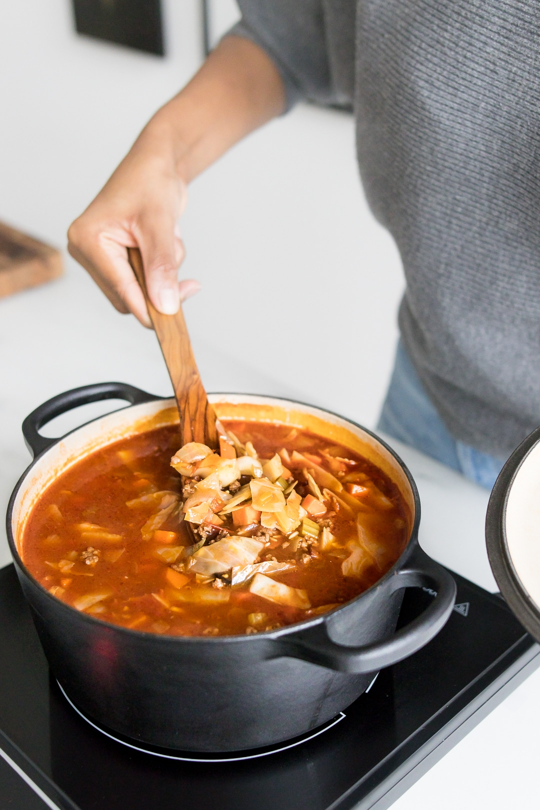 Mystique stirring cabbage roll soup in a black dutch oven pot.