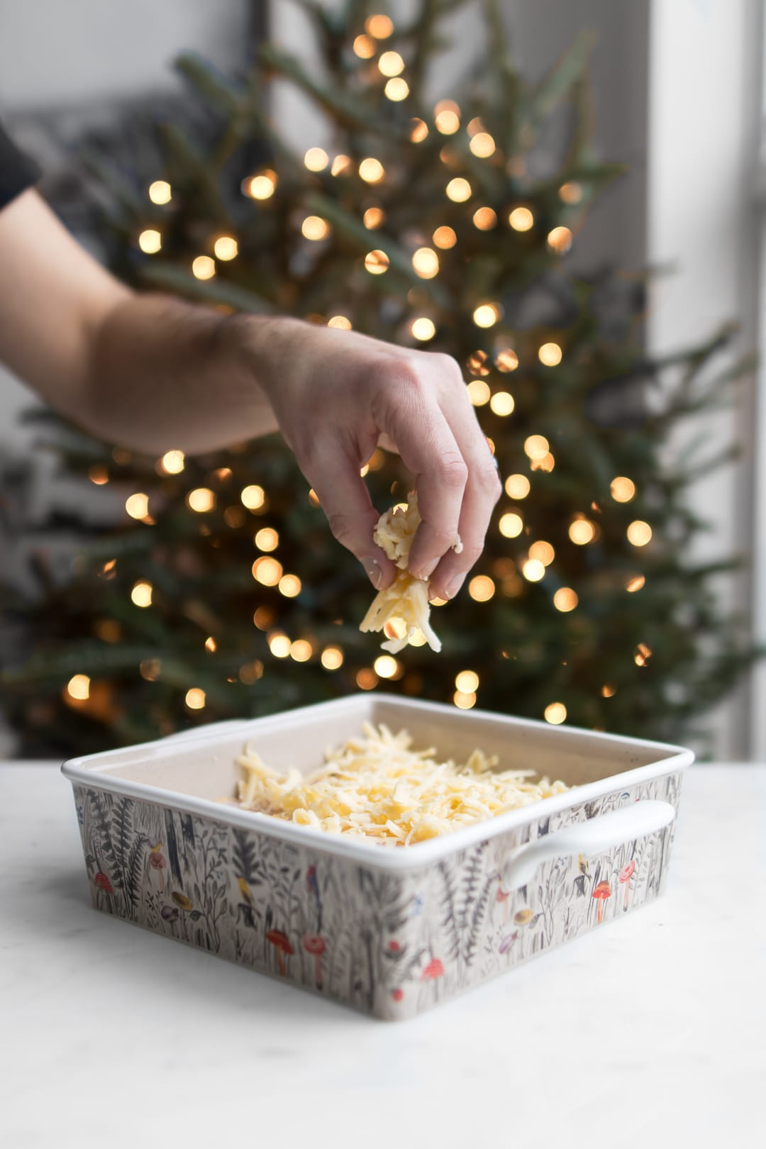 Philip's hand sprinkling cheese on wife saver with Christmas tree in the background