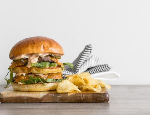 Image of the homemade big mac on a wood board with chips and napkin and lots of white space