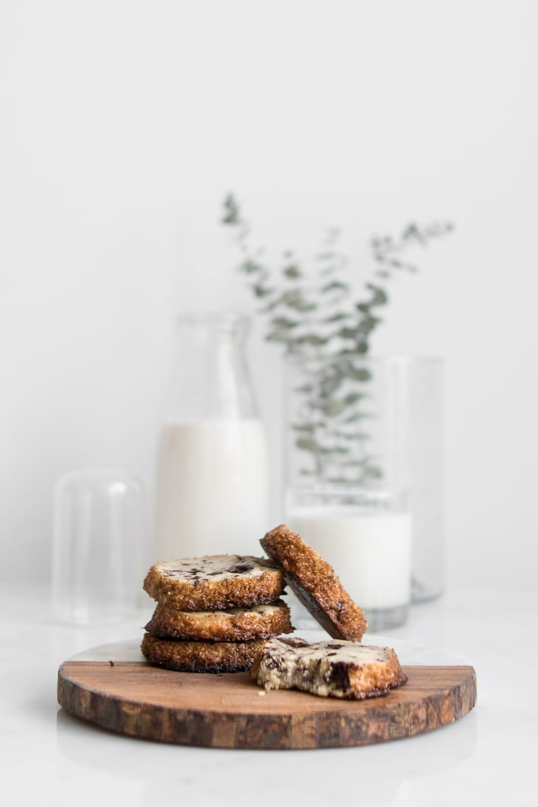 Dining In Cookbook Review - Chocolate Chunk Shortbread Cookies on a wood board with milk in the background