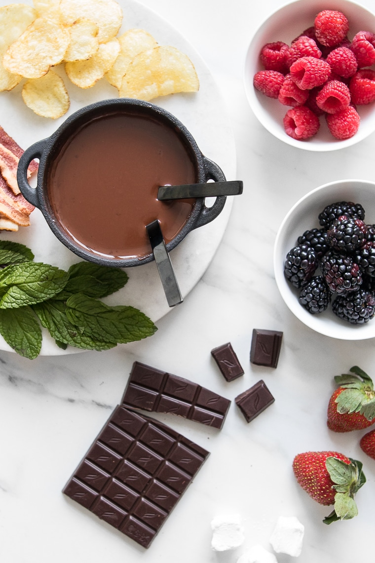 Dark Chocolate Fondue for Two in a small cast iron pot surrounded by a chocolate bar, mint leaves, chips, strawberries, and bowls of raspberries and blackberries