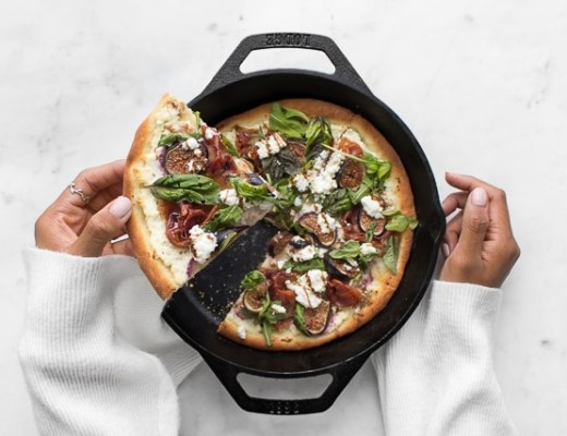 Mystique pulling out a piece of Fig and Prosciutto Pizza from a cast iron pan
