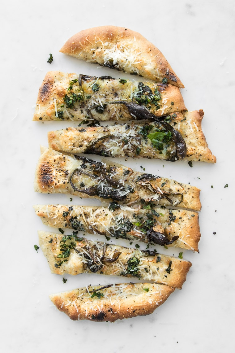Sliced Cacio e Pepe Pizza with Spring Ramps on a white marble table