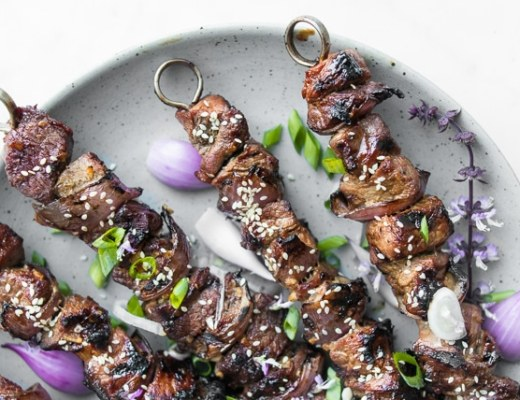 Close up of BBQ Beef Kebabs on a plate with red onions