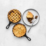Two curry beef pot pies in small skillets and a plate with a serving of the beef pot pie