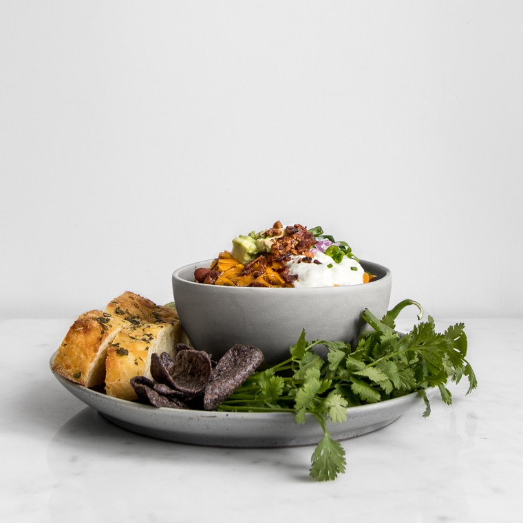 Side angle of a filled bowl of chili topped with cheese, sour cream and jalapenos