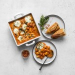 Baked gnocchi with vodka sauce being served with chunks of bread, basil, and chili flakes