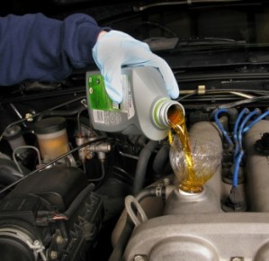 A person pouring oil to the car engine