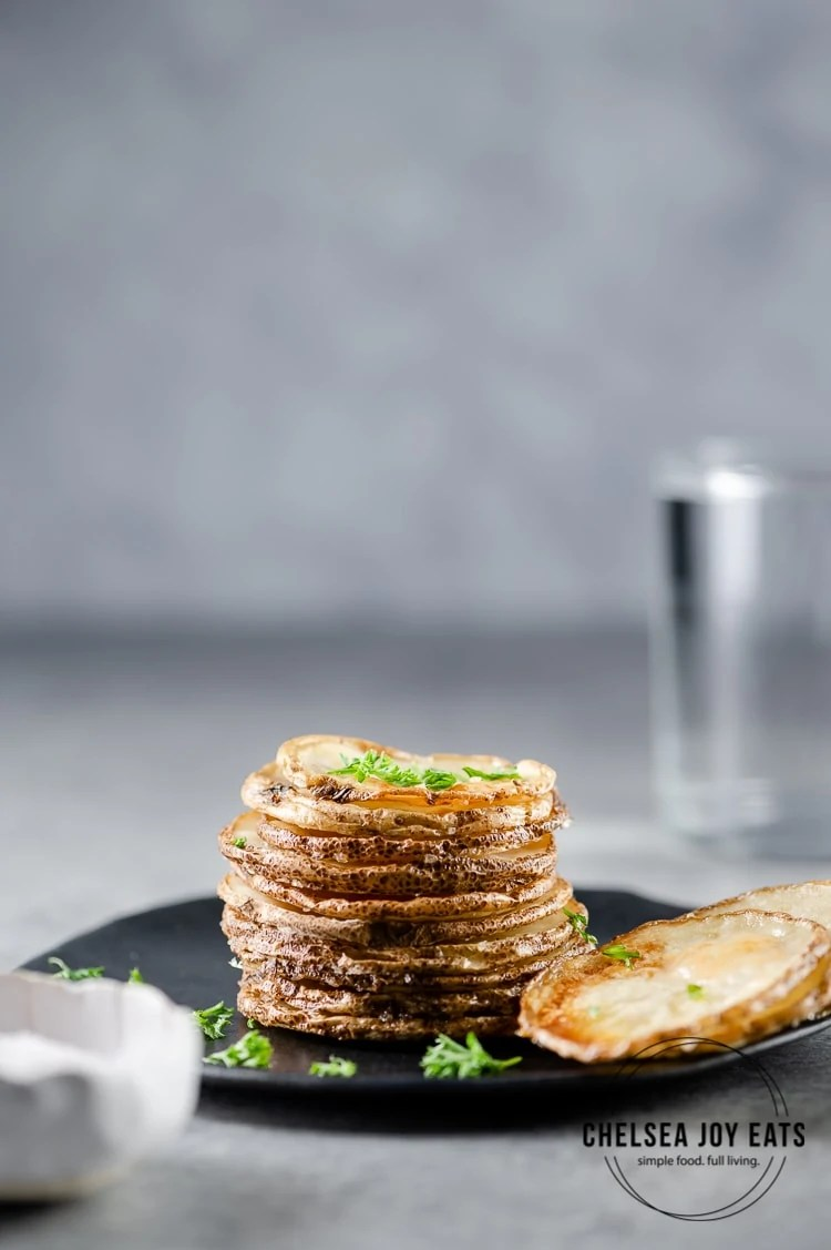 Stack of roasted potato rounds garnished with fresh parsley