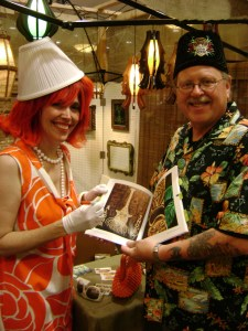 Cherry autographing a Tiki Art Now book for a fan.