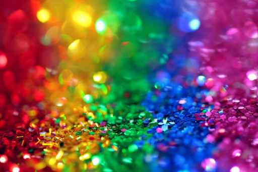 Assorted colored sequins, making a rainbow: red, yellow, green, blue, and purple. The rainbow is often associated with the LGBTQ+ community, which includes bi/pansexuality.