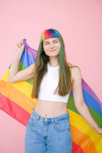 A woman with rainbow hair holds a gay pride flag. Is she queer enough?