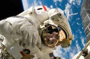 An astronaut floats in space with a spaceship and the Earth in the background.