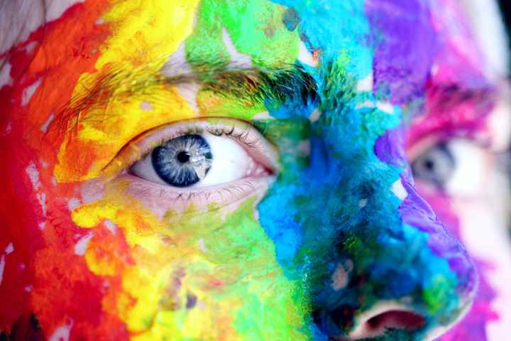 A close-up of a person with blue eyes, who has their face painted with rainbow colors, possibly in support of the LGBTQ+ community.