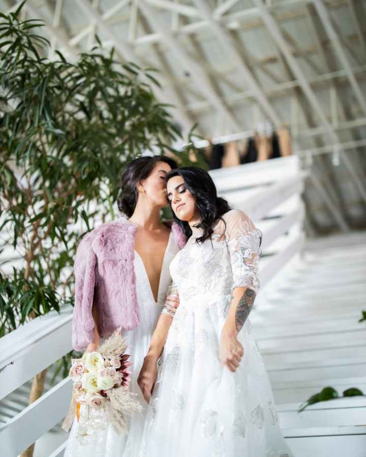 Two women in white bridal dresses descended a white staircase. The woman to the left of the frame wears a pink faux fur shawl and carries a bouquet of roses; she grasps the other woman's arm.