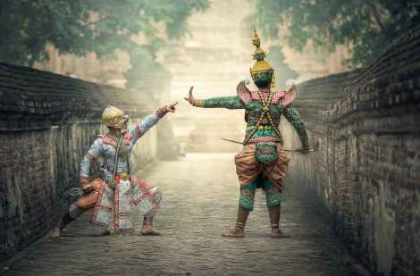 Two actors in elaborate traditional costumes enact a scene in front of stone walls. The actor on the left crouches while the actor on the right stands tall, arm outstretched toward the left of the frame.