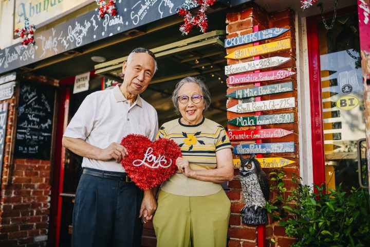 """An elderly couple smiles at the camera as they stand in front of a storefront, holding a red tinsel heart that reads """"love."""""""