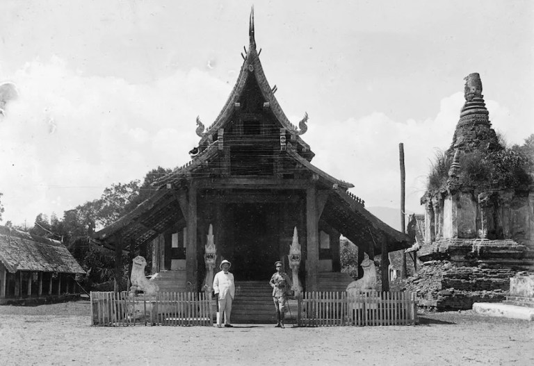 Two men in front of a temple