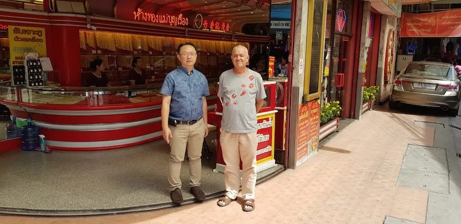 Two men in front of a gold shop