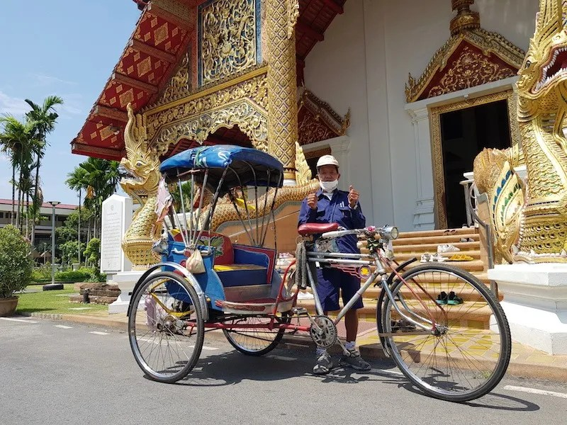 Man with bicycle taxi in front of temple