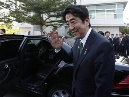 Japan's Prime Minister Shinzo Abe waves before he leaves the Thai-Nichi Institute of Technology in Bangkok
