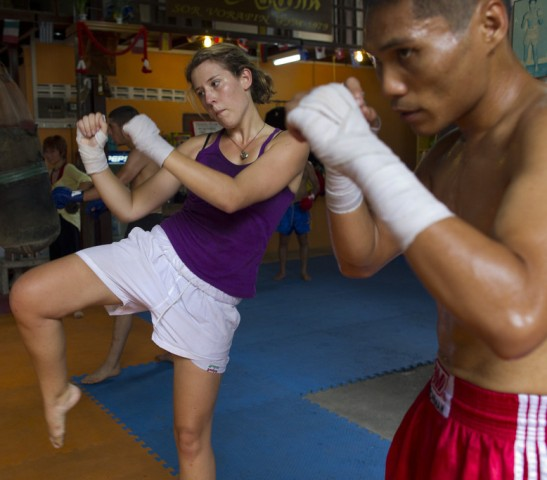 Dana Cleary from Tasmania, Australia gets instruction from Tak, a Thai kickboxing instructor, in a Muay Thai kickboxing class at the Sor. Vorapin kickboxing gym