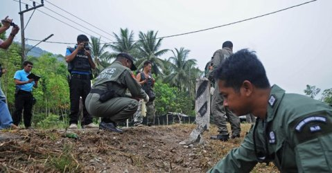 Thai bomb squad members inspect the site of a roadside bomb attack by suspected separatist militants. More than 5,000 people have been killed in nine years of bloodshed in Thailand's Muslim-majority south near the border with Malaysia, with shadowy insurgent groups blamed for near-daily bombings and shootings.—Photo by AFP