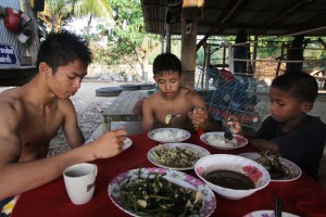 Chai (center) is shown at breakfast after his morning training with other fighters. He spends most of his day at the gym