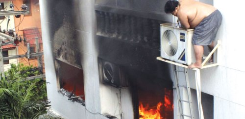 A resident waits for assistance on the third floor of a Bangkok apartment that caught fire in Chatuchak district. He was later rescued by fire-fighters, but a guest jumped to her death, trying to escape the blaze.