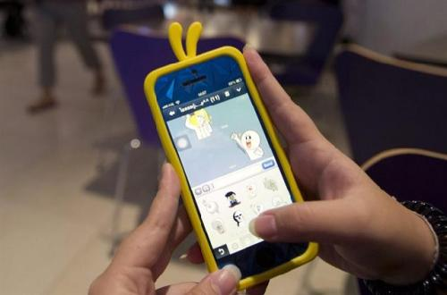 """A Thai teenager uses the """"Line"""" instant messaging app on her smartphone Tuesday, Aug. 13, 2013 in Bangkok, Thailand. Thai police asked the operator of the popular app for access to records of online chats, raising concerns about intrusive surveillance despite promising only suspected criminals would be targeted."""