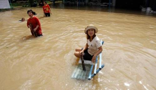 A woman sits on a bench in a flooded street at Srimahaphot district east of Bangkok - Source: Reuters