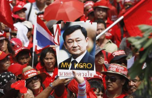 Demonstrators hold portraits of former Thai Prime Minister Thaksin Shinawatra during an anti-government protest outside the Government House in Bangkok February 24, 2009. Thousands of protesters marched on Thailand's seat of government to demand that Thai Prime Minister Abhisit Vejjajiva step down, adding to his troubles as the economy slides into recession.